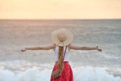 Dziewczyna stojaki na brzeg ocean szeroko rozpościerać ręki ujawnienia zawodnik bez szans zmierzchu czas widok z powrotem Zdjęcia Stock