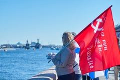Dziewczyna stojaki na bulwarze w St Petersburg i chwyta rosjaninie zaznaczają zwycięstwo Fotografia Royalty Free