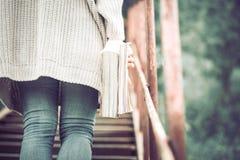 Dziewczyna stojaki na krokach schody z książką Zdjęcie Stock