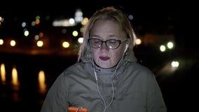 Dziewczyna stojaki na noc deptaku w szkłach, hełmofonach, nucić coś i tanczyć trząść jego głowę zbiory wideo