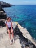 Dziewczyna stojaki na skałach, kołysają i spojrzenia przy morzem karaibskim fotografia stock