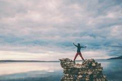 Dziewczyna stojaki na stosie kamienie i spojrzenia przy morzem fotografia royalty free