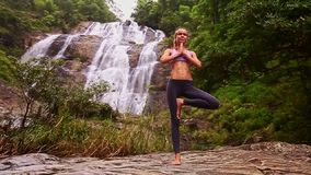 Dziewczyna stojaki w joga pozyci na mieszkanie kamieniu siklawą zbiory wideo