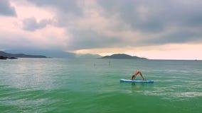 Dziewczyna stojaki w pozie posyłają chył na paddleboard w oceanie zbiory wideo