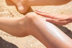 Dziewczyna stosuje sunscreen na nodze fotografia royalty free