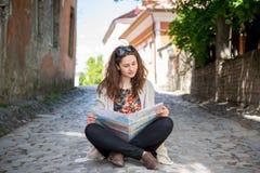 Dziewczyna studiuje mapę podczas gdy siedzący na ziemi Zdjęcia Royalty Free