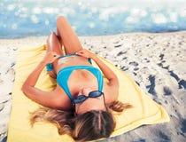 Dziewczyna sunbathing na plaży na ręczniku Lata pojęcie zdjęcie royalty free