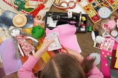 Dziewczyna szy lalę odziewa, odgórny widok, szwalni akcesoria odgórny widok, szwaczki miejsce pracy, dużo protestuje dla uszycia  Fotografia Royalty Free