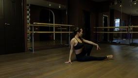 Dziewczyna tancerz z ponytail w czarnych rajstopy demonstruje cia?o elastyczno?? robi ?wiczenie wyczynu plecy na pod?ogowym zwoln zdjęcie wideo