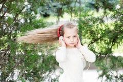Dziewczyna taniec muzyka w lato parku Mały dziecko cieszy się muzykę w hełmofonach plenerowych Dzieciaka tancerz z długim latając zdjęcia stock