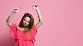 Dziewczyna taniec przeciw menchii ścianie z uśmiechem, cieszenie dobry nastrój obrazy stock