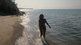 Dziewczyna tanowie na plaży i bieg zbiory wideo