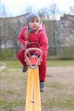 Dziewczyna teeters na seesaw Zdjęcie Royalty Free