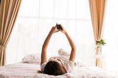 Dziewczyna texting w jej łóżku w domu Zdjęcia Royalty Free