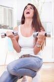 Dziewczyna trenuje mocno w domu z ciężarami Fotografia Stock