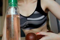 Dziewczyna trząść bicep w sporta wierzchołku, butelka ciecz zdjęcia stock