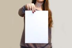 Dziewczyna trzyma białego A4 pustego papier pionowo Ulotki presentati Zdjęcia Stock