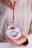 Dziewczyna trzyma Bożenarodzeniową piłkę w pięknym trykotowym pulowerze obrazy royalty free