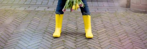 Dziewczyna trzyma bukiet świezi wiosna tulipany stara miasto ulica inicjuje gumowego kolor żółty Uwalnia przestrzeń dla teksta zdjęcie royalty free