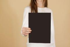Dziewczyna trzyma czarnego A4 pustego papier pionowo Ulotki presentati Zdjęcie Royalty Free