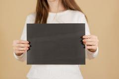 Dziewczyna trzyma czarnego A4 pustego papier pionowo Ulotki presentati Zdjęcia Stock