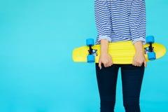 Dziewczyna trzyma deskorolka, widok od plecy Zdjęcia Royalty Free