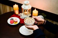 Dziewczyna trzyma filiżankę cappuccino i deseru macaroons na talerzu Obraz Royalty Free