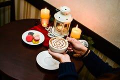 Dziewczyna trzyma filiżankę cappuccino i deseru macaroons na talerzu Obrazy Royalty Free