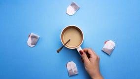 Dziewczyna trzyma filiżankę kawy otaczająca herbacianymi torbami Pojęcie napoje i preferencje Kawowa fermata, przerwa zdjęcia stock