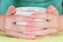 Dziewczyna trzyma filiżankę kawy w ręce z różowymi gwoździami gel połysk zdjęcie royalty free
