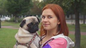 Dziewczyna trzyma jej mopsa i ono uśmiecha się przy kamerą zbiory
