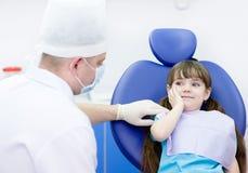 dziewczyna trzyma jej policzek z toothache przy dentysty offi zdjęcia stock