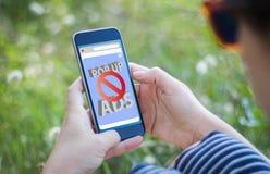dziewczyna trzyma jej smartphone z reklama blokerem w trawie obrazy royalty free