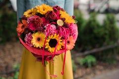 Dziewczyna trzyma kolorowego bukiet z różnym Gerbera kwiatem Obrazy Stock