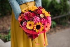 Dziewczyna trzyma kolorowego bukiet z różnym Gerbera kwiatem Zdjęcia Stock