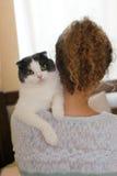 Dziewczyna trzyma kota na jej ramieniu w domu Zdjęcia Royalty Free