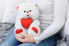 Dziewczyna trzyma misia pluszowego białego niedźwiedzia w białym pulowerze obraz royalty free