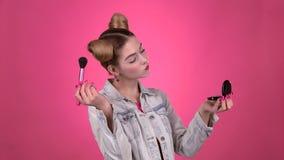 Dziewczyna trzyma muśnięcie w jej ręce i pudruje jej twarz Różowy tło zbiory