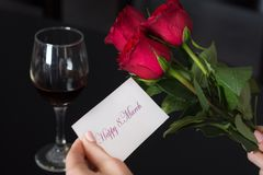 Dziewczyna trzyma papierową kartę z wiadomością Szczęśliwi 8 Marzec w jej ręki, czerwieni wina i róży szkle na czerń stole i zdjęcia royalty free