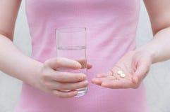 Dziewczyna trzyma pigułkę i szkło woda fotografia stock