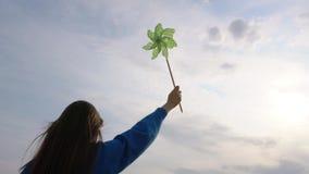 Dziewczyna trzyma pinwheel w ręce przeciw tłu niebo zbiory