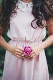 Dziewczyna trzyma różowi różanego w jej rękach Zdjęcia Stock
