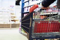 Dziewczyna trzyma rękojeść karmowy kosz, iść między rzędami w supermarkecie Kosze na ko?ach parking obrazy stock