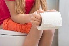 Dziewczyna trzyma rolkę papier toaletowy w ona ręki Zdjęcie Royalty Free