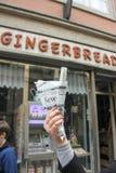 Dziewczyna trzyma słodką pamiątkarską opłatek rolkę w gazecie na tle gingerbreas kawiarni sklep fotografia stock