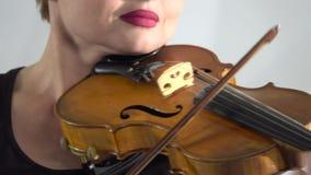 Dziewczyna trzyma skrzypce bawić się jej kłonienie nad sznurkami z bliska Biały tło zbiory