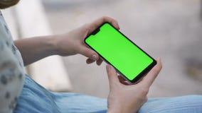 Dziewczyna trzyma smartphone horizontally i ogląda wideo na ekranie Zielony parawanowy smartphone dla tropić zbiory wideo