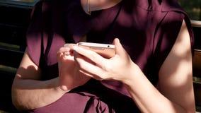 Dziewczyna trzyma smartphone który używa komunikować w ogólnospołecznych sieciach Kobieta palce dotykają ekran sensorowego zdjęcie wideo