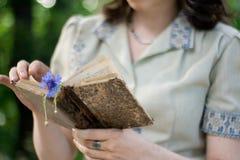 Dziewczyna trzyma starą książkę w rocznik sukni obrazy stock
