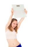 Dziewczyna trzyma waży w jego ręce i raduje się swój osiągnięcia, Fotografia Stock